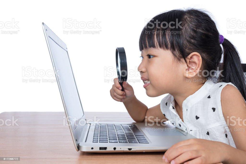 Asiática chinês menina olhando portátil através de lupa - foto de acervo
