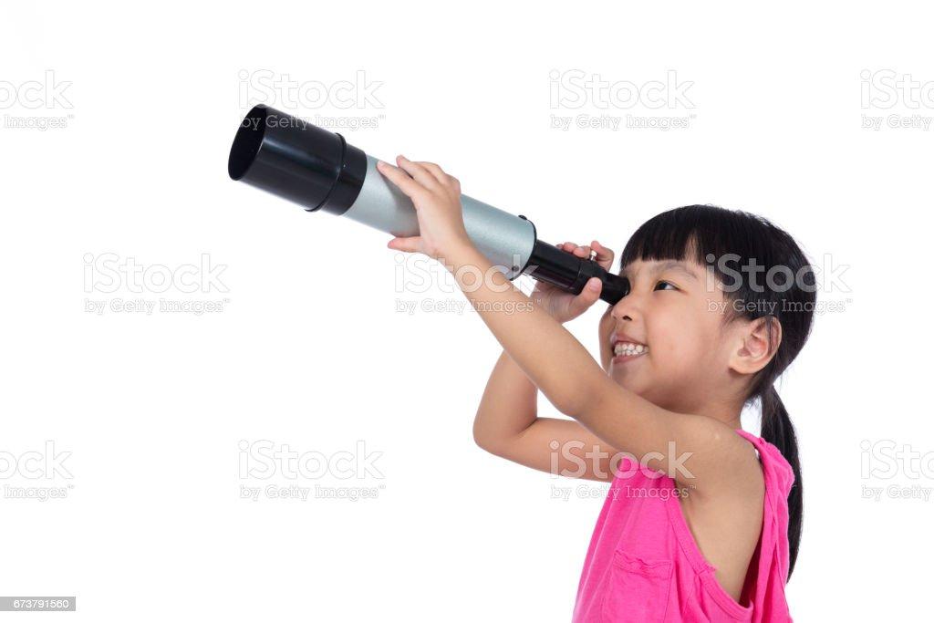 Asiatique chinoise petite fille regardant à travers un télescope photo libre de droits