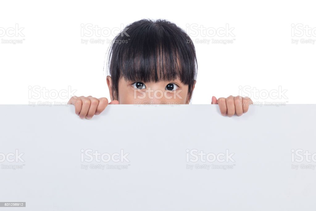 Asian Chinese little girl peeping behind white board stock photo