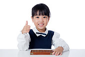 Asian Chinese little girl playing abacus in isolated white background