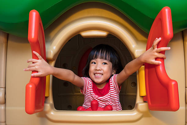 asian chinese little girl playing in toy house - heimerziehung stock-fotos und bilder