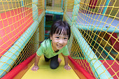 Asian Chinese little girl playing slide at indoor playground alone