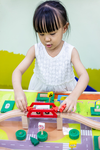 Asian Chinese little girl playing wooden toy train at indoor playground