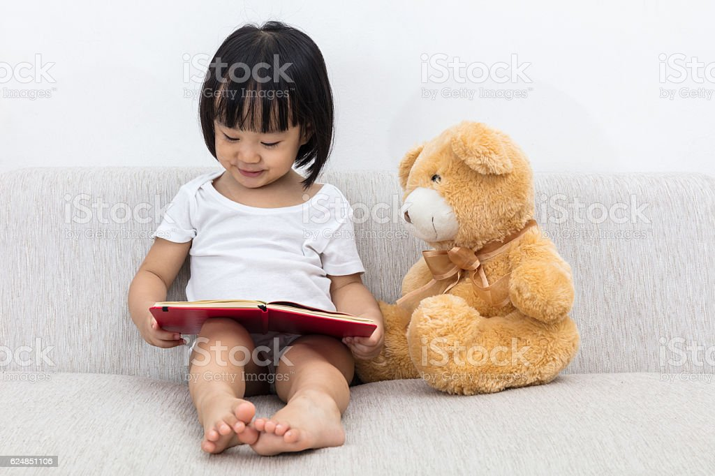 Asian Chinese little girl reading book with teddy bear stock photo