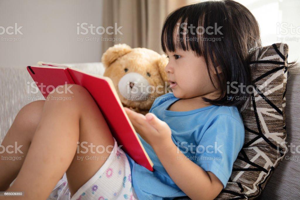 亞洲中國小女孩讀書與泰迪熊圖像檔