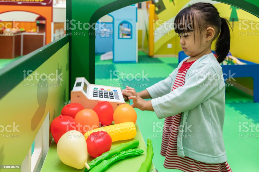 Asian Chinese little girl role-playing at fruits store stock photo
