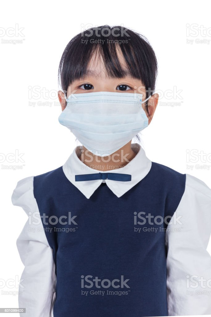 Asian Chinese little primary school girl wearing a protective mask stock photo