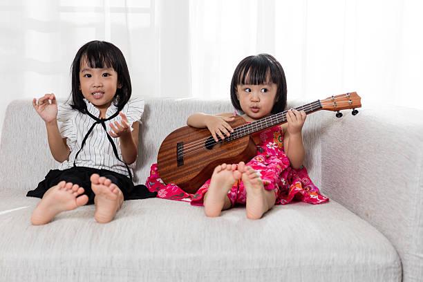 asian chinese little sister playing ukele - ukulele songs stock-fotos und bilder