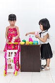 Asian Chinese little sisters pretending as customer and cashier with trolley toys in isolated white background.