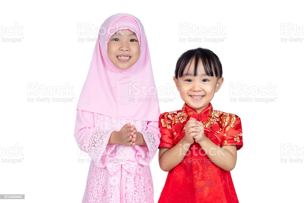 Asian Chinese little sisters wearing cheongsam and traditional Malay costume with greeting gesture stock photo
