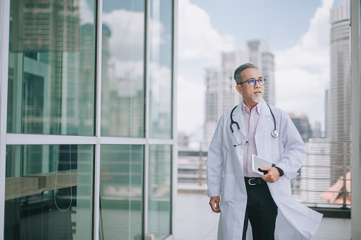 asian chinese male doctor walking towards his office