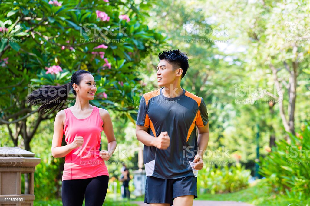Asian Chinese man and woman jogging in city park stock photo