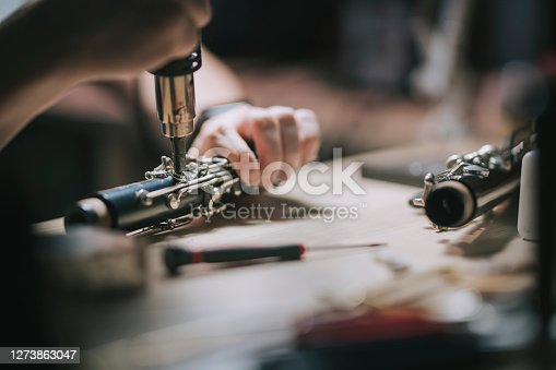 Asian chinese man checking and repairing saxophone music wind instrument in his workshop
