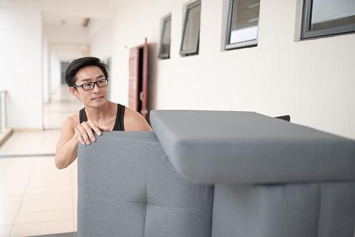 Asian Chinese man using push cart moving sofa at office corridor.