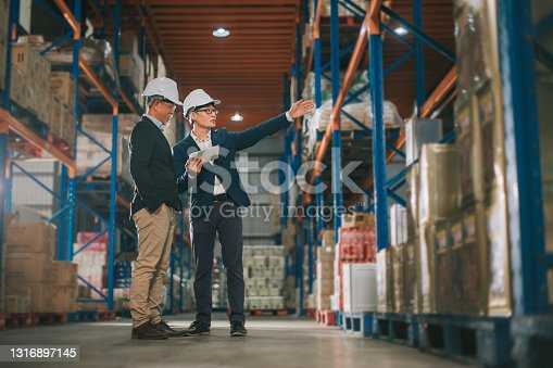 istock asian chinese management having discussion at warehouse with white hardhat using digital tablet 1316897145