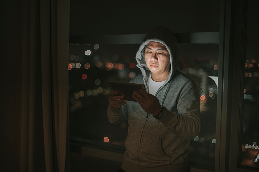 asian chinese mid adult male looking at digital tablet with worried face at living room sofa at night near window