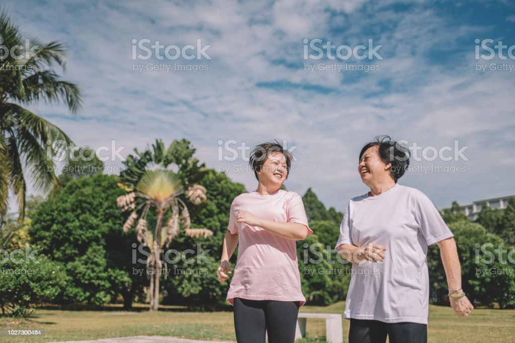 asian chinese mother and daughter doing exercise in the morning at the park stock photo