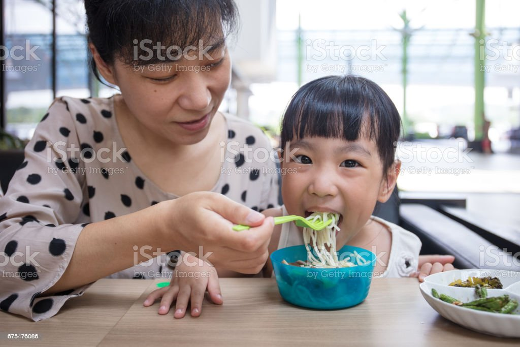 Asian Chinese mother and daughter eating beef noodles photo libre de droits