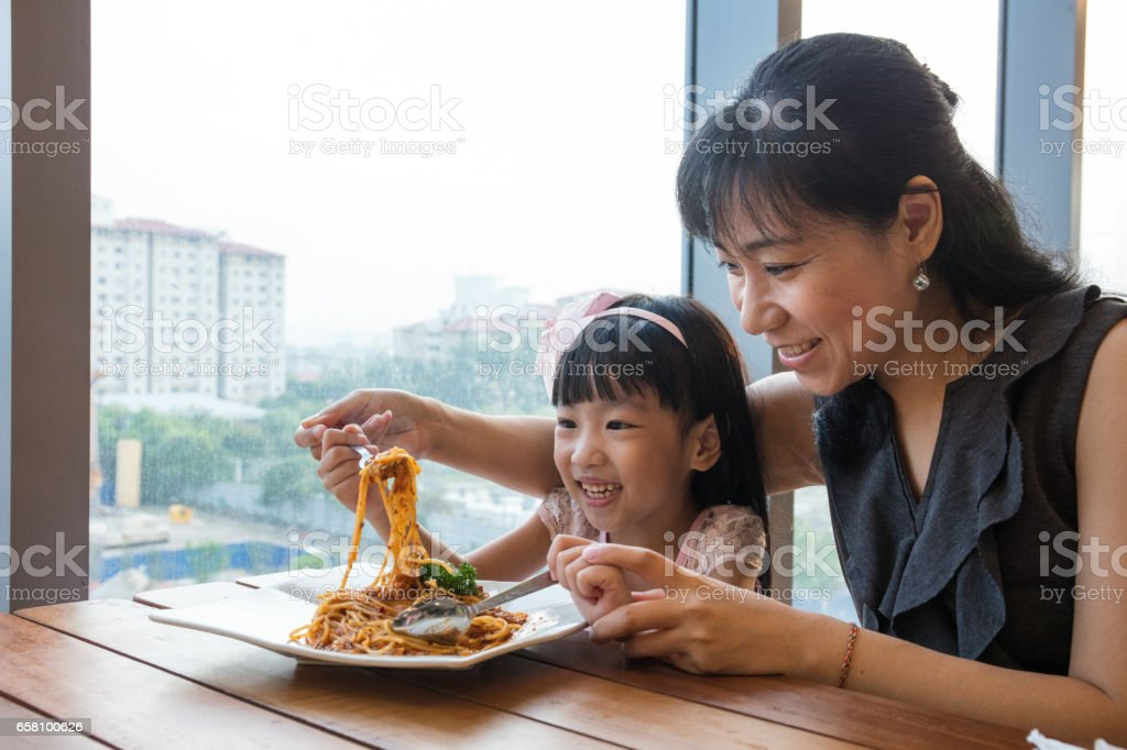 Asian Chinese mother and daughter eating spaghetti bolognese stock photo