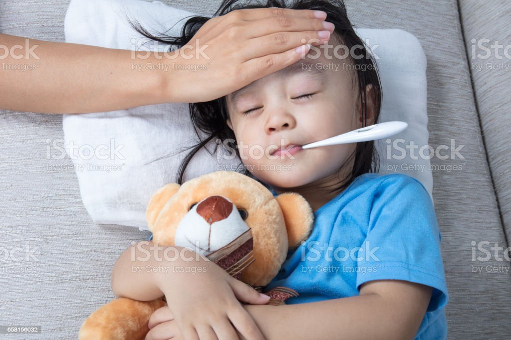 Asian Chinese mother measuring little girl forehead for fever stock photo