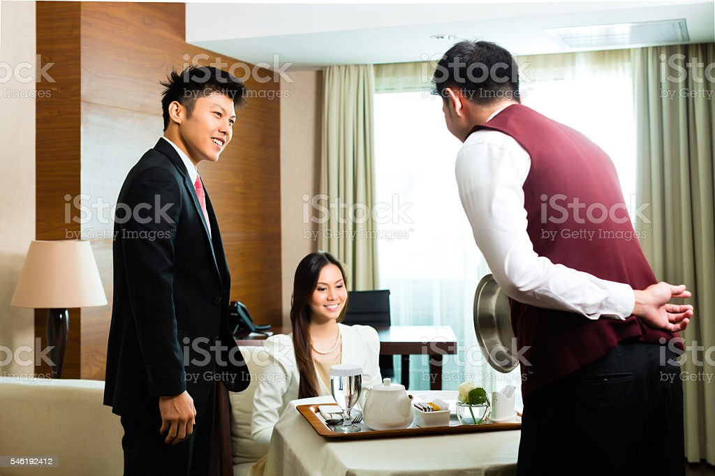 Asian Chinese room waiter serving food in hotel suite stock photo