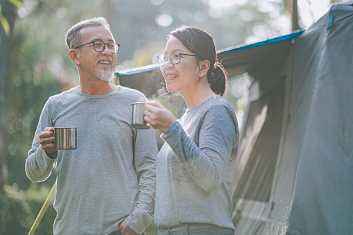 asian chinese senior couple enjoying morning freshness with cup of hot drink outside camping tent
