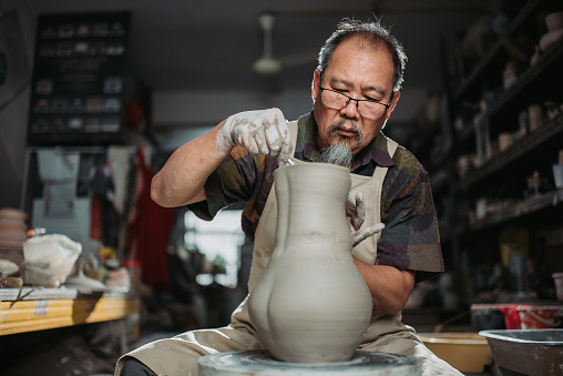 front view of active senior man, owner of the pottery studio looking down with both hands making pottery