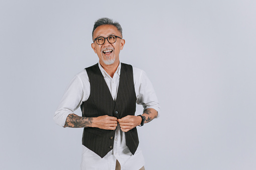 asian chinese senior man gray hair with hair stubble rolling up sleeves smiling happily gray background