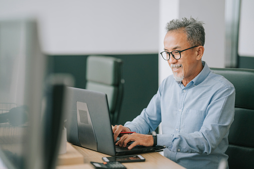 Asian chinese senior man with facial hair using laptop typing working in office open plan