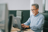 istock Asian chinese senior man with facial hair using laptop typing working in office open plan 1331469701