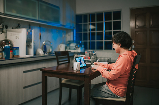 asian chinese senior woman talking to her son and daughter in law at night in kitchen video call using digital tablet telecommunicating