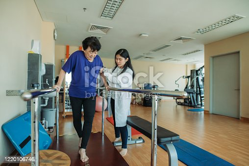 Asian chinese senior women practicing, holding parallel bars and walking while physical therapists helping at side in a rehab centre at hospital