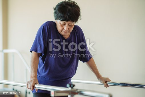 Asian chinese senior women practicing, holding parallel bars and walking in a rehab centre at hospital