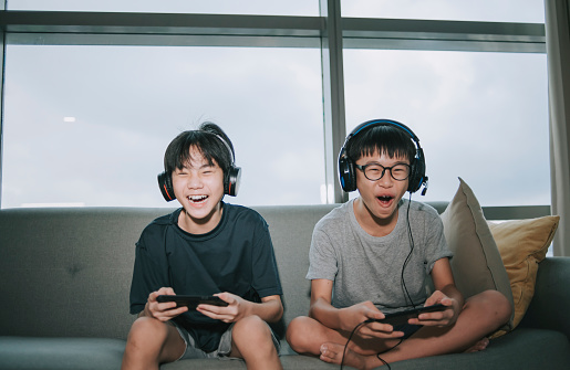 2 asian chinese sibling brother sitting on sofa playing online video games with headset in living room during weekend