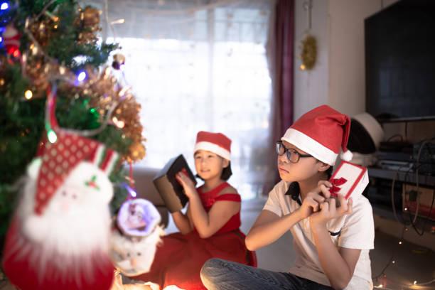 asiatische chinesische geschwister aufgeregt immer weihnachtsgeschenk - number 13 stock-fotos und bilder