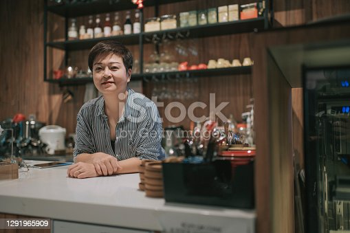 asian chinese small business owner at kitchen counter smiling looking at camera