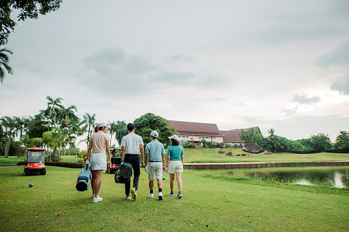 Asian chinese smiling family bonding, walking together on the golf course