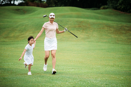 Asian chinese smiling young mother golfer bonding with holding daughter hand and running together on the golf course