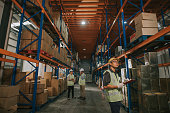 istock asian chinese warehouse worker looking checklist and management having discussion with warehouse worker at warehouse with white hardhat 1318322428