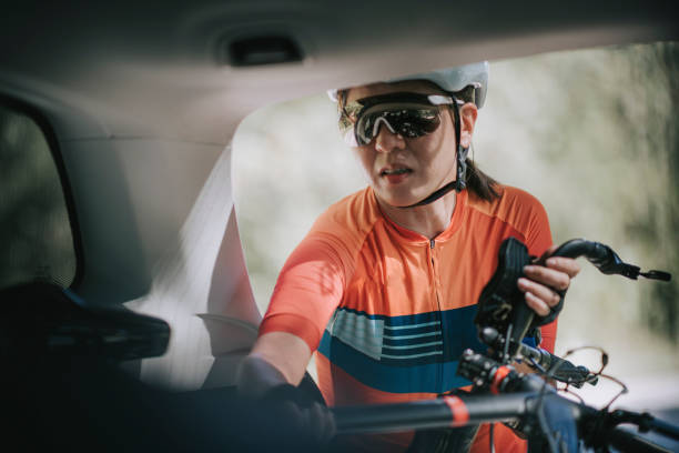 asian chinese woman professional cyclist taking down her bicycle from the SUV car trunk ready to cycle asian chinese woman professional cyclist taking down her bicycle from the car trunk ready to cycle mountain biking stock pictures, royalty-free photos & images