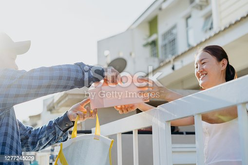 Asian Chinese woman receiving dessert order delivery from a deliveryman