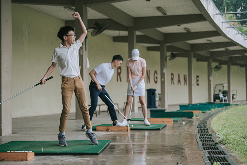 Asian chinese young boy practicing golf in driving range with his parents during raining