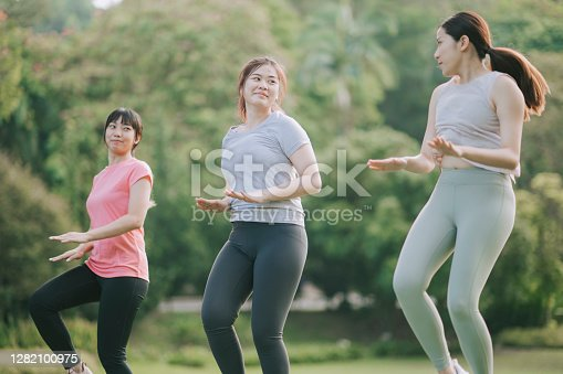 asian chinese young female warming up exercise in public park during weekend morning stretching bodies