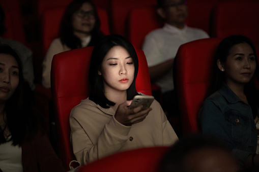 Asian Chinese young woman using smart phone while movie is showing in movie theater. Disturbing other audience around her