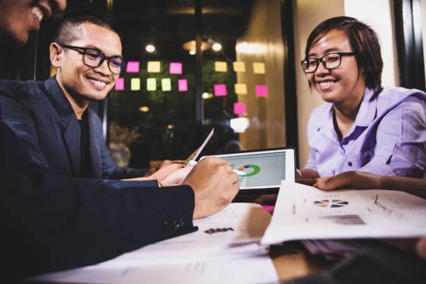 colegas asiáticos de lluvia de ideas en la oficina por la noche - foto de stock