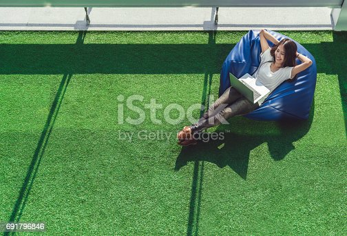 istock Asian college student or freelance woman using laptop computer, lying on bean bag in garden. University campus or park scene. Education or casual business concept. Copy space on green grass yard 691796846