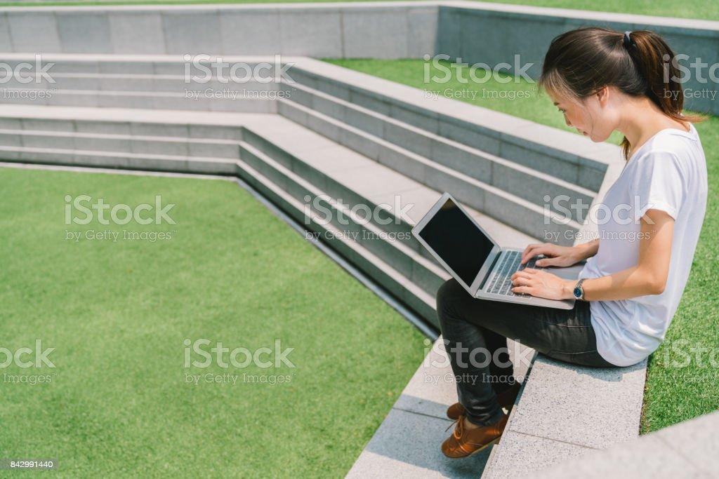 大学キャンパスやモダンな公園の階段でラップトップを使用してアジア大学学生やフリーランスの女性。情報技術、教育、またはカジュアルなビジネス コンセプト。緑の草の庭のスペースをコピーします。 ストックフォト