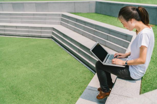 大学キャンパスやモダンな公園の階段でラップトップを使用してアジア大学学生やフリーランスの女性。情報技術、教育、またはカジュアルなビジネス コンセプト。緑の草の庭のスペースをコピーします。 - フリーランス ストックフォトと画像