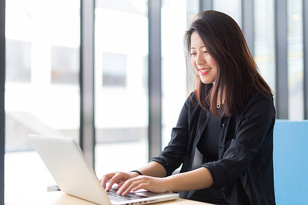 Asian college student sitting with a laptop stock photo