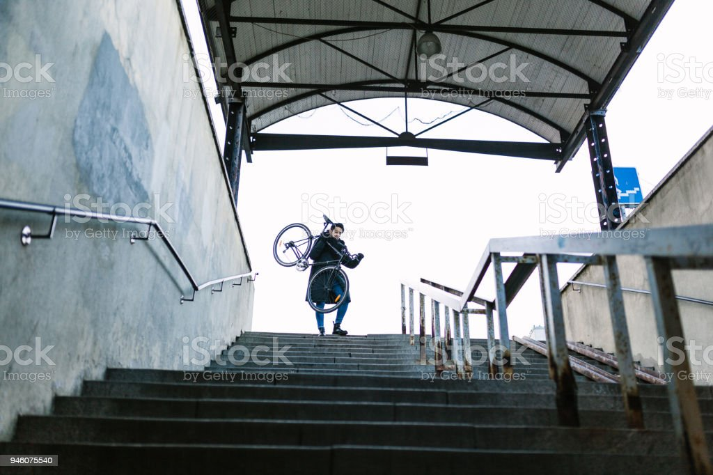 Asian commuter carrying the bike to the subway stock photo